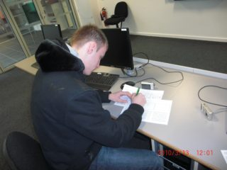 Student writing in IT Suite | West Herts College