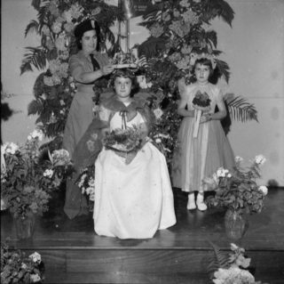 A girl guide crowns the stately Rose Queen with her lady-in-waiting in attendance | © Watford Observer 1964